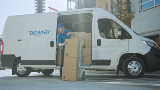 courier opens delivery van side door and takes out cardboard box package, closes the door and goes on delivering postal parcel. - furgone video stock e b–roll
