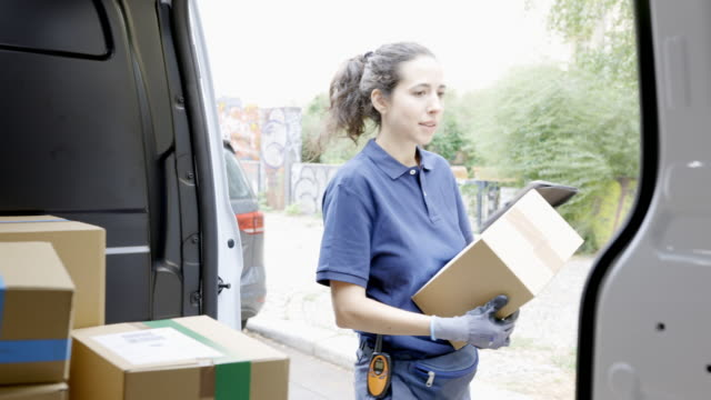 courier person goes on delivering a parcel - furgone video stock e b–roll