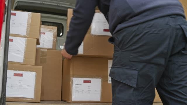 vídeos de stock e filmes b-roll de courier stacking the packages onto the cart - entregar
