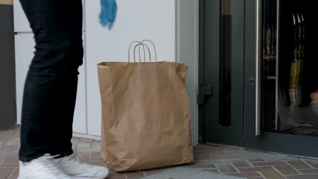 kurye giyen eldiven karantina sırasında gıda temassız teslimat gerçekleştirir - sahanlık stok videoları ve detay görüntü çekimi
