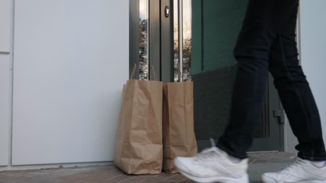 kurye giyen eldiven müşterilerine kapı gıda temassız teslimat gerçekleştirir - sahanlık stok videoları ve detay görüntü çekimi