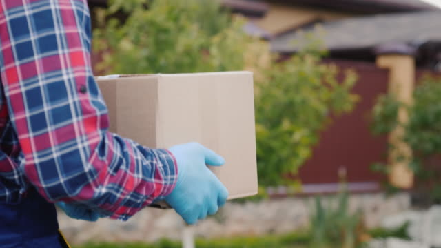 A courier with a parcel of hands walks along the street. He's wearing protective gloves. video