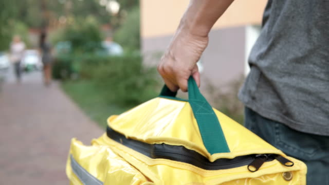 A courier with a yellow backpack delivers an online order. Stay home, self-isolation. video