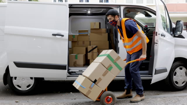 courier worker moving cardboard boxes on a cart - furgone video stock e b–roll