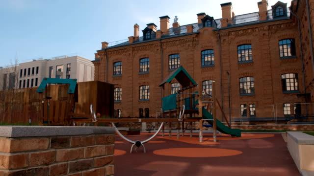 innenhof mit spielplatz im bereich von mehrfamilienhäusern - kinderspielplatz stock-videos und b-roll-filmmaterial