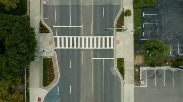 Covid 19 Shelter In Place - Empty Crosswalk Aerial view looking down on a deserted community park due to the corona virus mandate to shelter at home and follow social distancing. The primary focus is on the empty crosswalk except for one pedestrian. stay home stock videos & royalty-free footage
