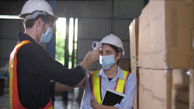 Covid-19 coronavirus symptoms checking temperature at Manufacturing warehouse