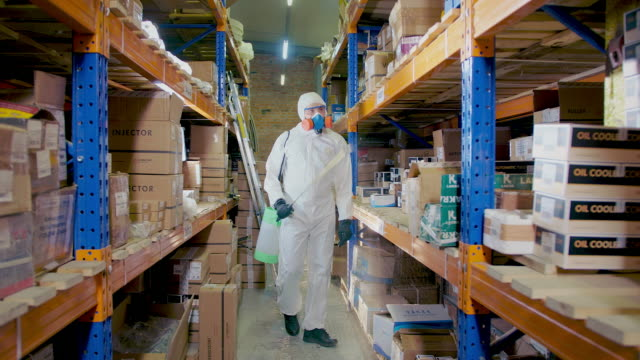 Covid-19. Person White Protect Suit Disinfect Storehouse. Corona virus Measures. video