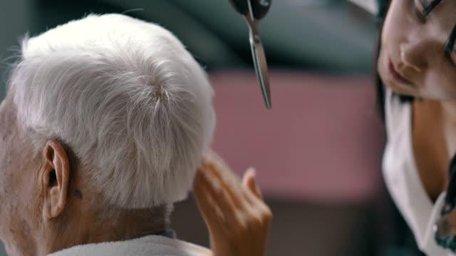 covid-19 quarantäne : großeltern bekommen einen haarschnitt von enkelin zu hause - friseur lockdown stock-videos und b-roll-filmmaterial