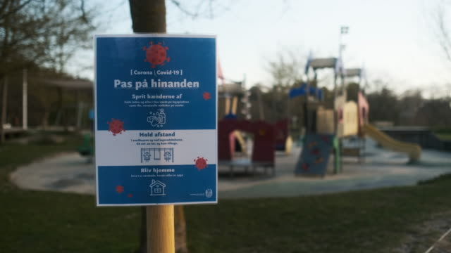 Covid-19 Sign By Closed Children'S Park Lockdown Wide Shot Of Poster Saying 'Take Care Of Each Other' With Hygiene Instructions In Front Of Children'S Play Area In Park During Covid-19 (Coronavirus) Quarantine Period denmark stock videos & royalty-free footage