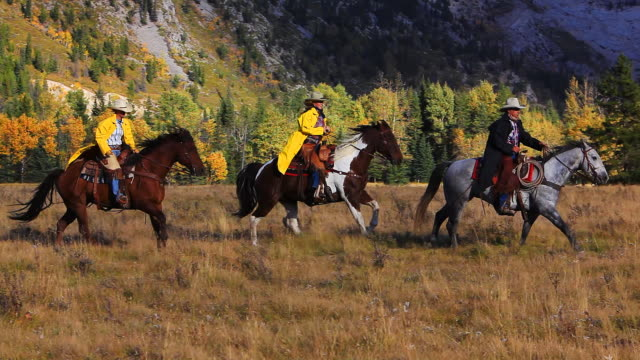 Cowboy and Cowgirls galloping on horseback through the mountain foothills video