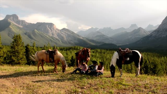 cowboy/cowgirls pausa nel prato di montagna - cowgirl video stock e b–roll
