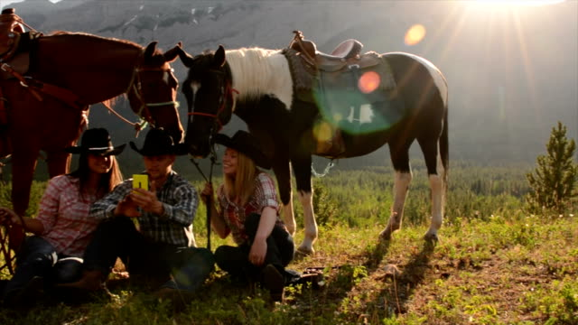 Cowboy/ cowgirls pause in mountain meadow Cowboy/ cowgirls pause in mountain meadow, use smart phone horseback riding stock videos & royalty-free footage