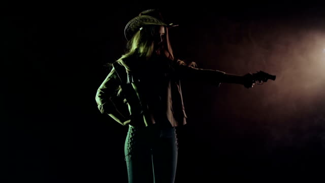 Cowboy girl takes out a revolver and makes a shot. Black smoke background. Slow motion. Side view video