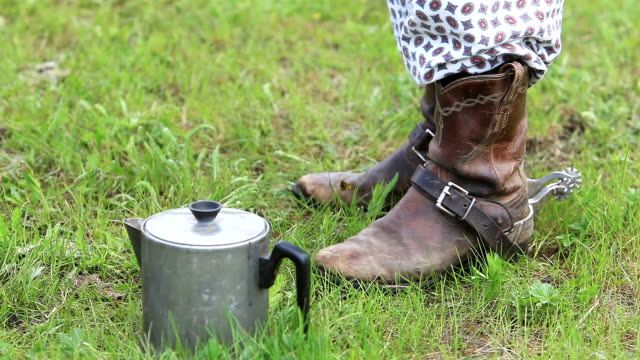 Cowboy in pajamas wearing boots and spurs having coffee