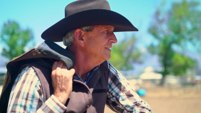 cowboy leaning on a fence and holding jacket in rodeo arena - cowboy video stock e b–roll