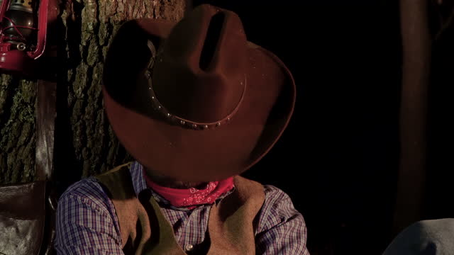 Cowboy prepares to sleep in the woods at night