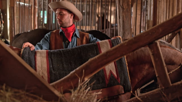 DS Cowboy putting a saddle pad on horse in stall video