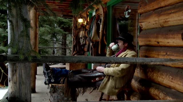 cowboy vita sul portico esterno log cabin - cowboy video stock e b–roll
