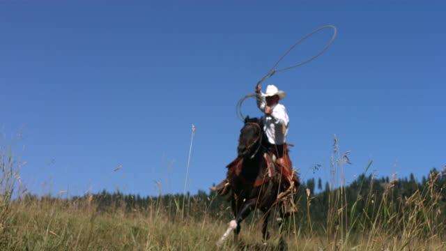 stockvideo's en b-roll-footage met cowboy swings lasso, slow motion - alleen één mid volwassen man