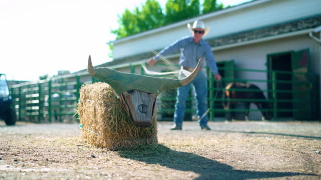 Cowboy training lassoing on a ranch