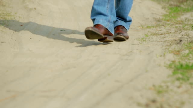 cowboy walking on the sandy road. - rodeo stock videos and b-roll footage