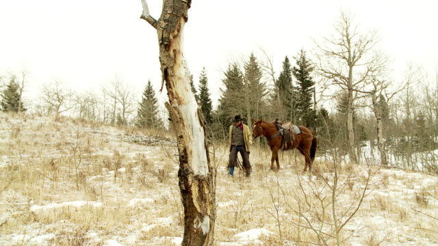 Cowboy with his horse in the snow during winter