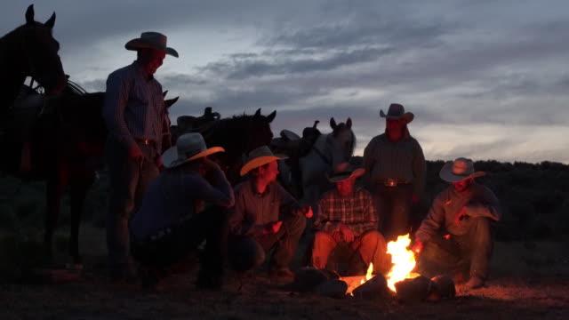 cowboys around a camp fire. - настоящая жизнь стоковые видео и кадры b-roll