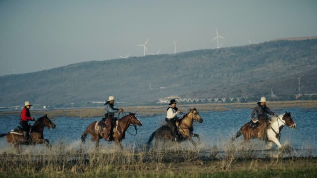 Cowboys riding horse in wild field