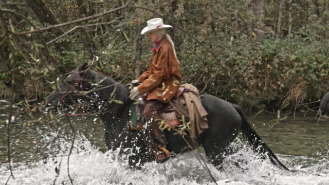 SLO MO DS Cowboys riding horses across river