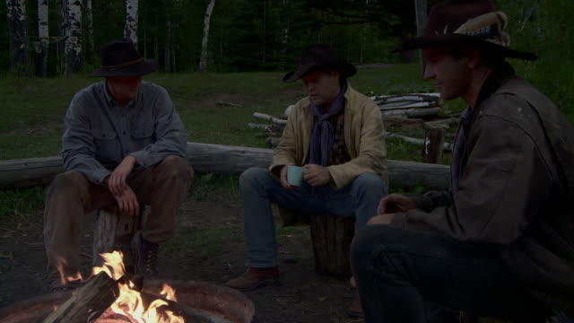 cowboys sit around a fire video