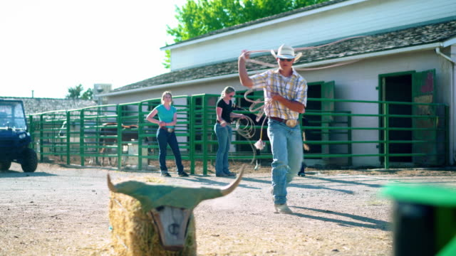 Cowboys training lassoing on a ranch