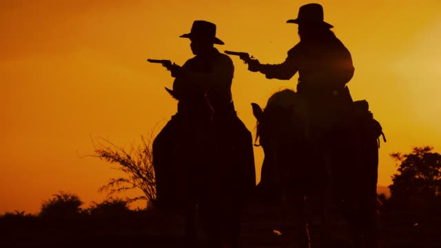 cowboys with revolver riding horses - ovest video stock e b–roll