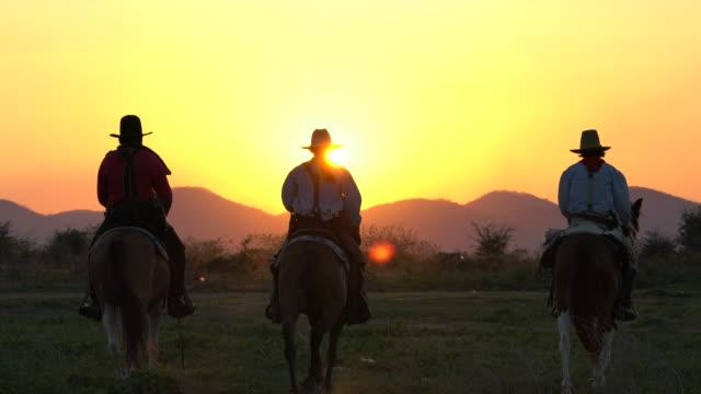 cowboys with revolver riding horses - запад стоковые видео и кадры b-roll