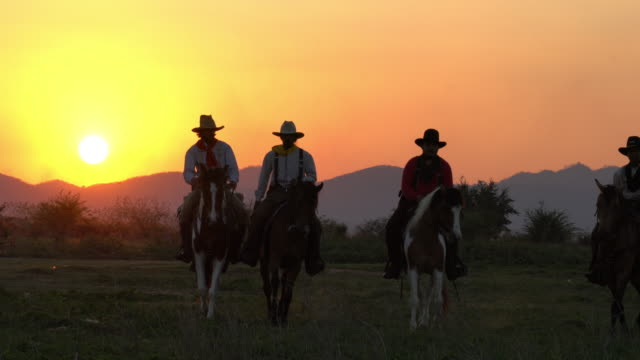 Cowboys with revolver riding horses