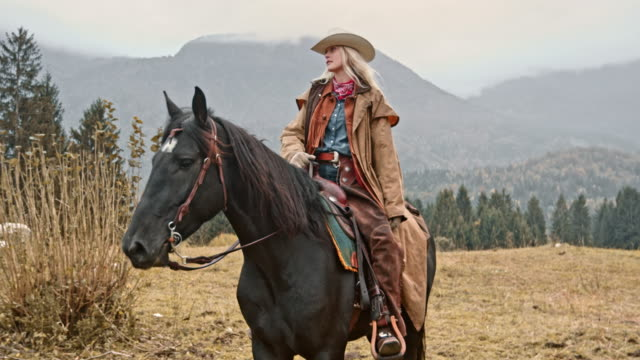 slo mo cowgirl riding her horse on mountain - cowgirl video stock e b–roll