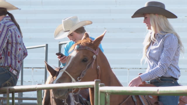 cowgirls on their cellphones waiting to compete - cowgirl video stock e b–roll
