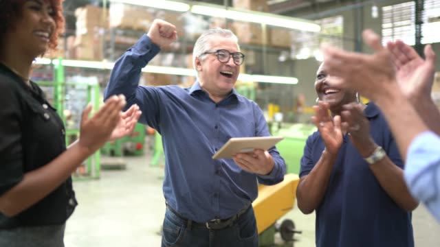 Coworkers celebrating some good news in a factory