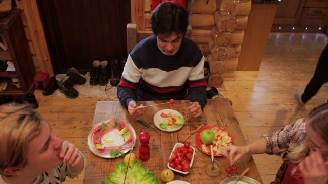 stockvideo's en b-roll-footage met collega's eten diner in een blokhut - christmas cabin