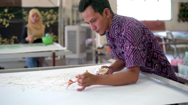 stockvideo's en b-roll-footage met collega's schilderij in een batik-atelier - maleisië