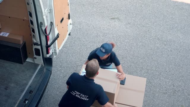 coworkers rushing to load packages in a delivery van - furgone video stock e b–roll