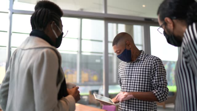 coworkers talking and using digital tablet on office's lobby - with face mask - businessman covid mask video stock e b–roll