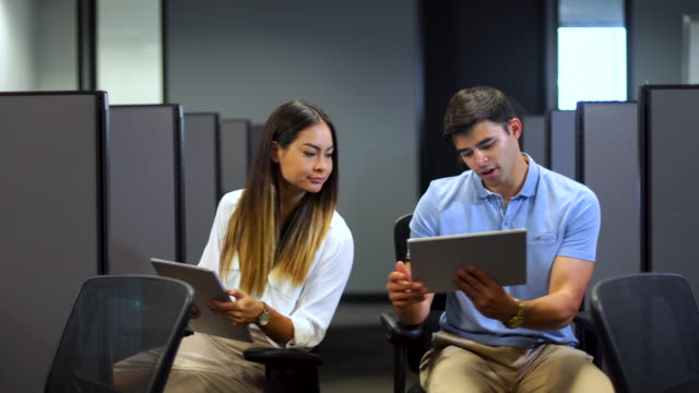 Coworkers Using Digital Devices at their Office Cubicles Coworkers Sharing Digital Data at the Office. Young financial businessman and businesswoman sitting at their cubicles sharing data off their laptops and digital tablet. office cubicle stock videos & royalty-free footage