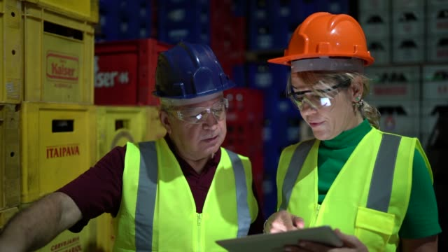 Coworkers walking and using digital tablet at warehouse Coworker walking and using digital tablet at warehouse manufacturing occupation stock videos & royalty-free footage