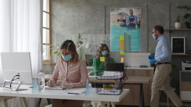Coworkers with protective face masks using computer in bank office
