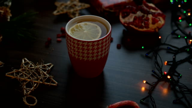 Cozy christmas decoration on black wooden table. Christmas lights, tea. Top view, Dolly shot video
