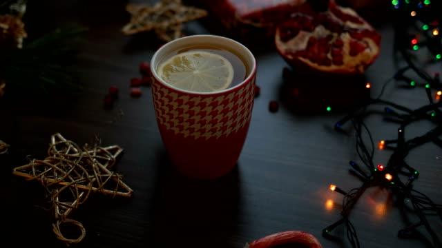 Gemütlichen Weihnachts-Dekoration auf schwarzer Holztisch. Weihnachtsbeleuchtung, Tee. Ansicht von oben geschossen Dolly – Video
