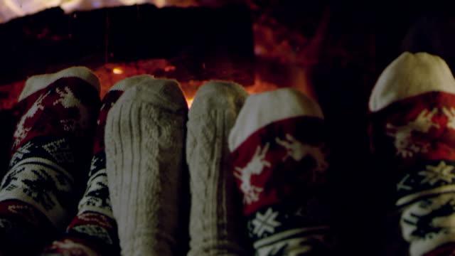 4K Cozy feet in Christmas socks by fireplace, slow motion video