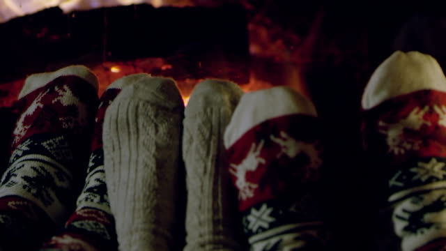 4K Cozy feet in Christmas socks relaxing by cozy fireplace, slow motion video