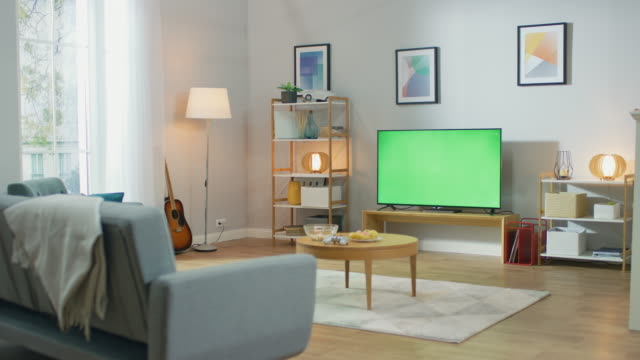 vídeos de stock e filmes b-roll de cozy living room with stylish furniture and design, green chroma key tv in the middle of the room. - sala